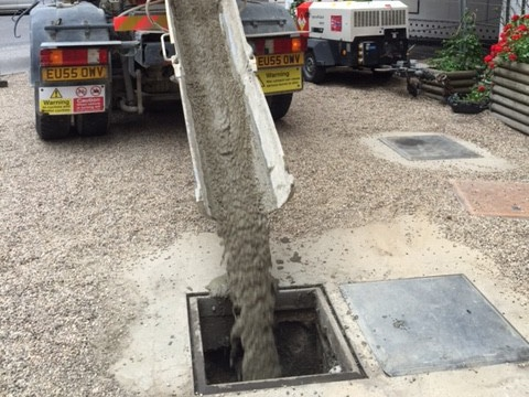 Concrete being gravity fed into a redundant petrol tank.